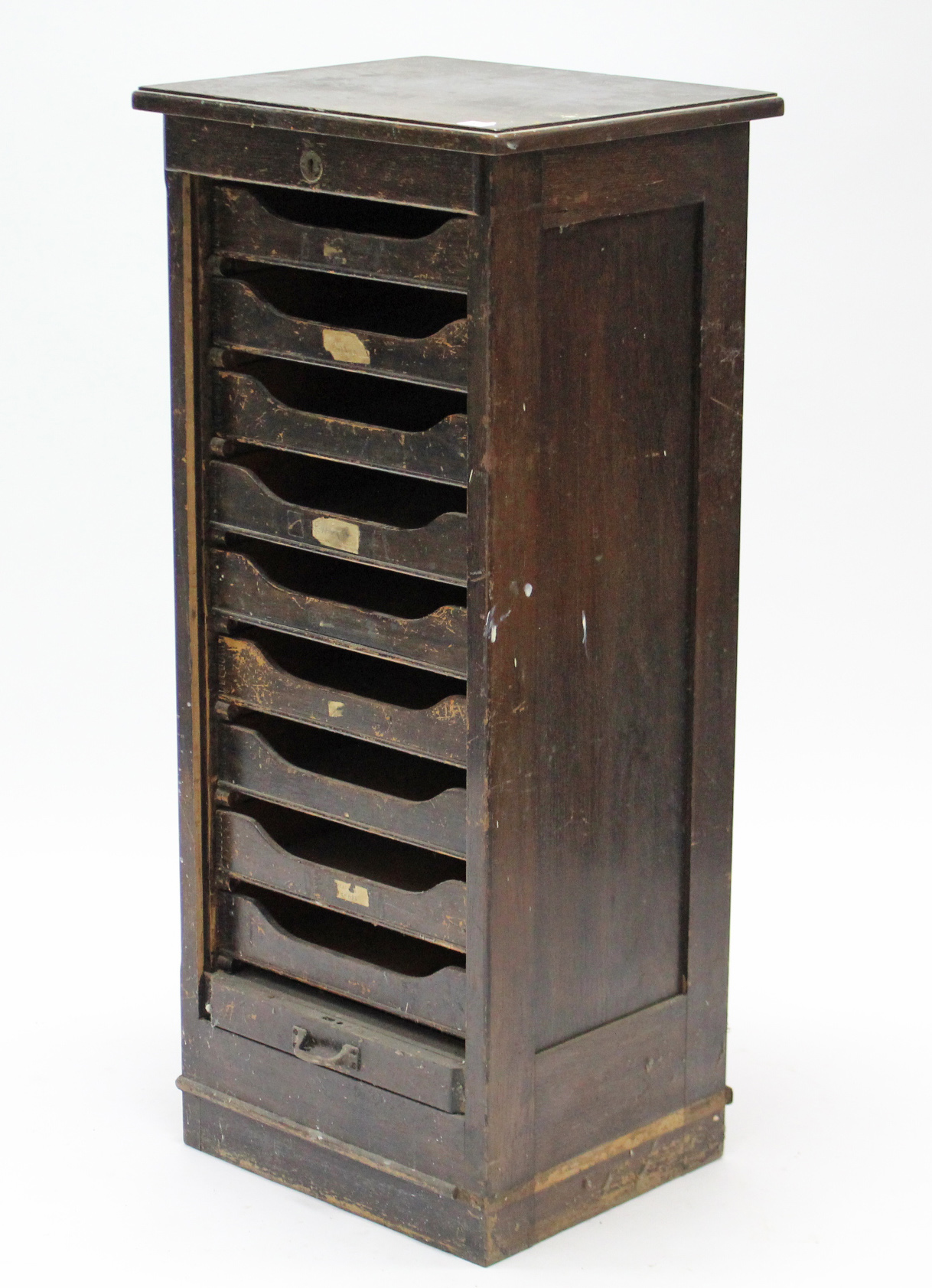 Lot 51 - An Edwardian oak small upright office cabinet, fitted nine sliding trays enclosed by tambour