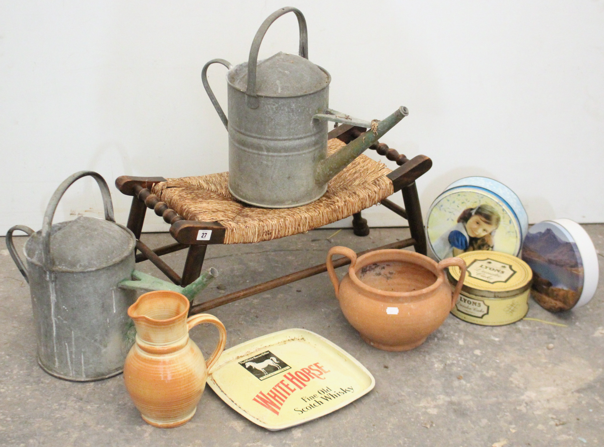 """Lot 27 - A string-seat stool; two galvanised-metal watering cans; a """"White Horse"""" scotch whisky advertising"""