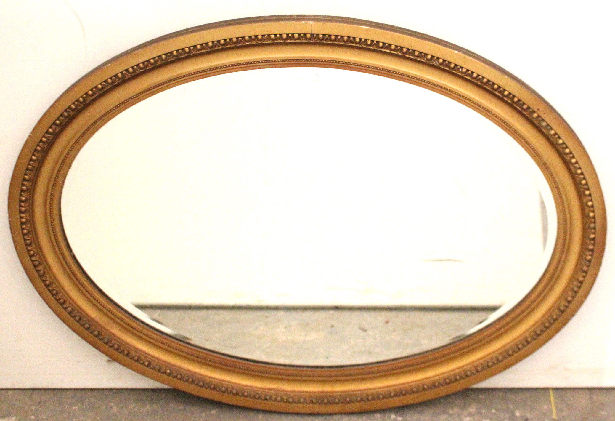"Lot 41 - A gilt frame oval wall mirror with egg-&-dart border, & inset bevelled plate, 25"" x 34¾""."