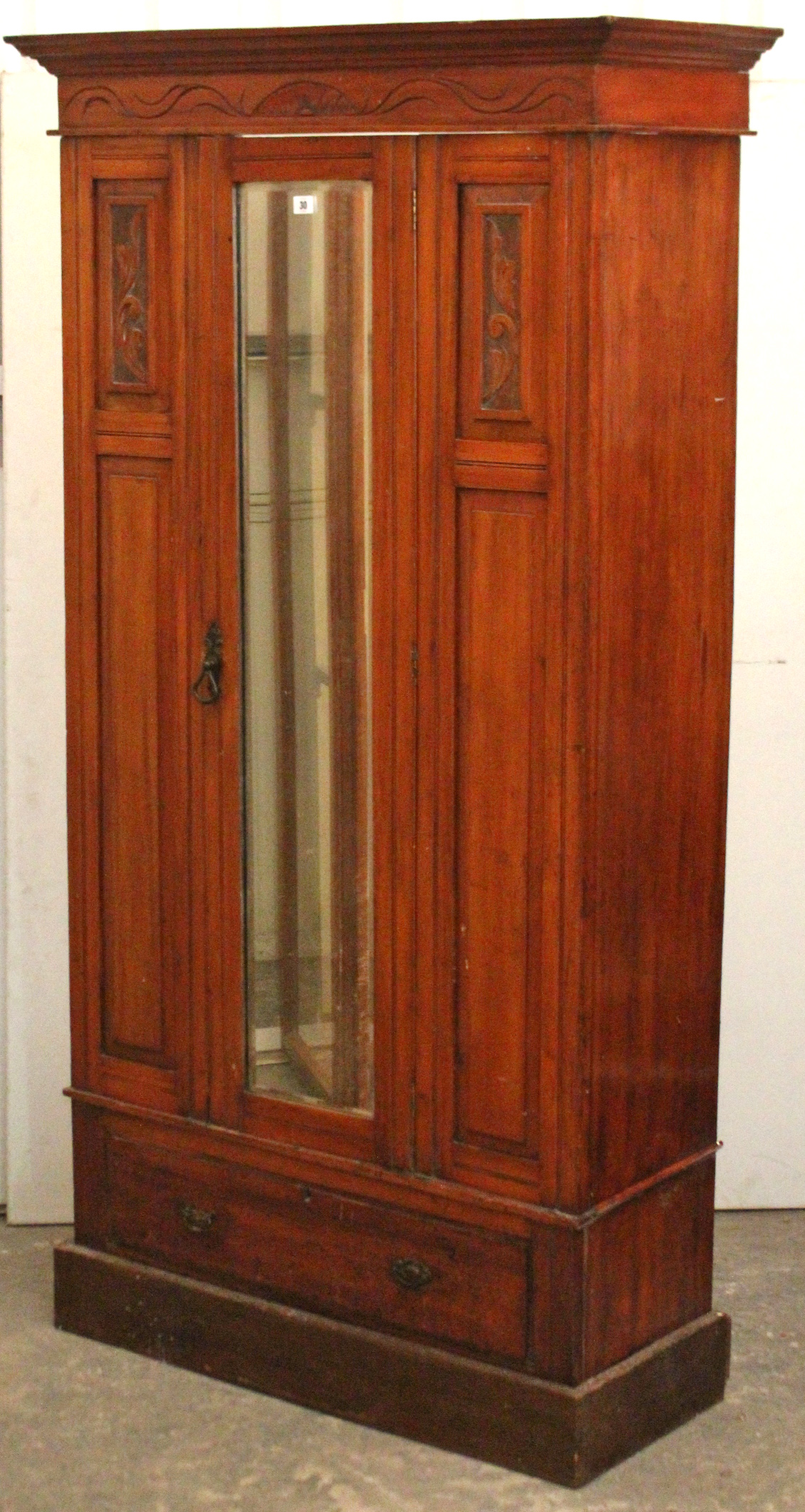 Lot 30 - A late Victorian carved mahogany small wardrobe enclosed by rectangular bevelled mirror door to