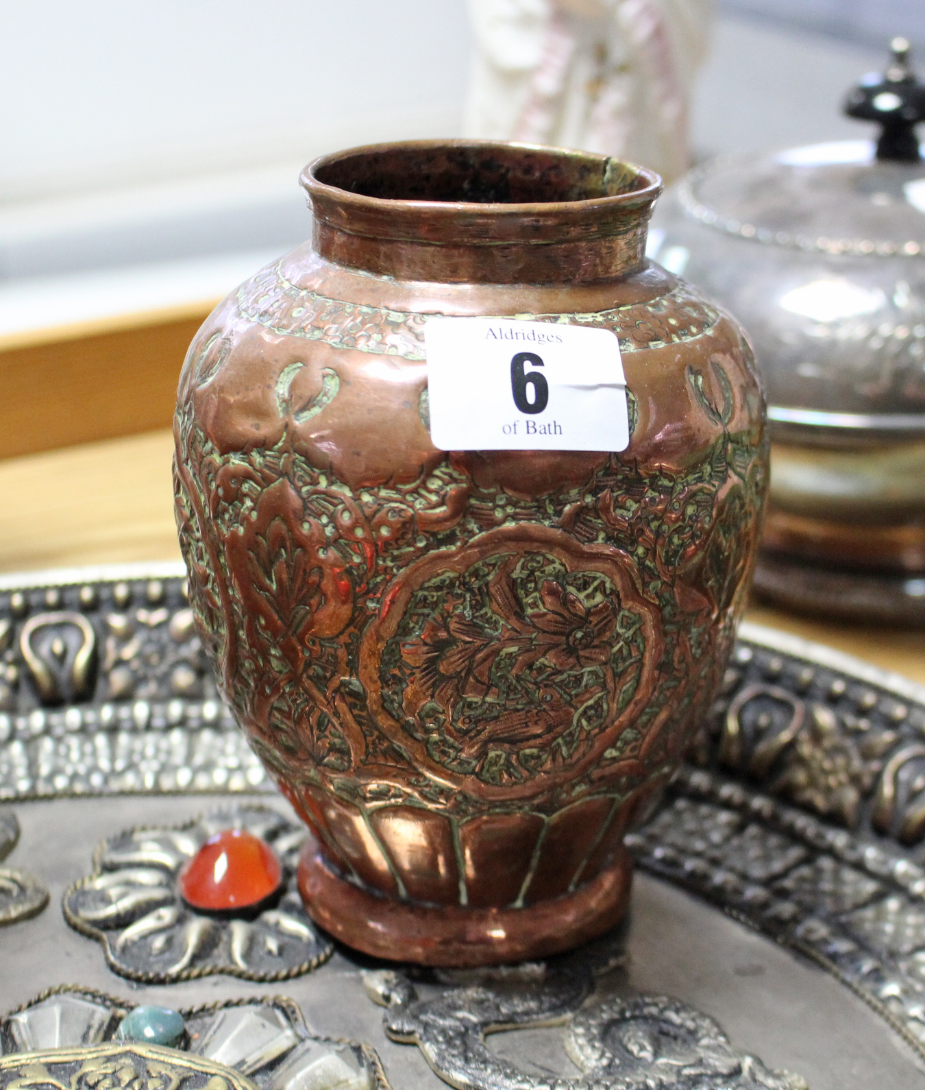 "Lot 6 - A Copper ovoid vase with embossed floral design, 5½"" high; an eastern silvered-metal circular"
