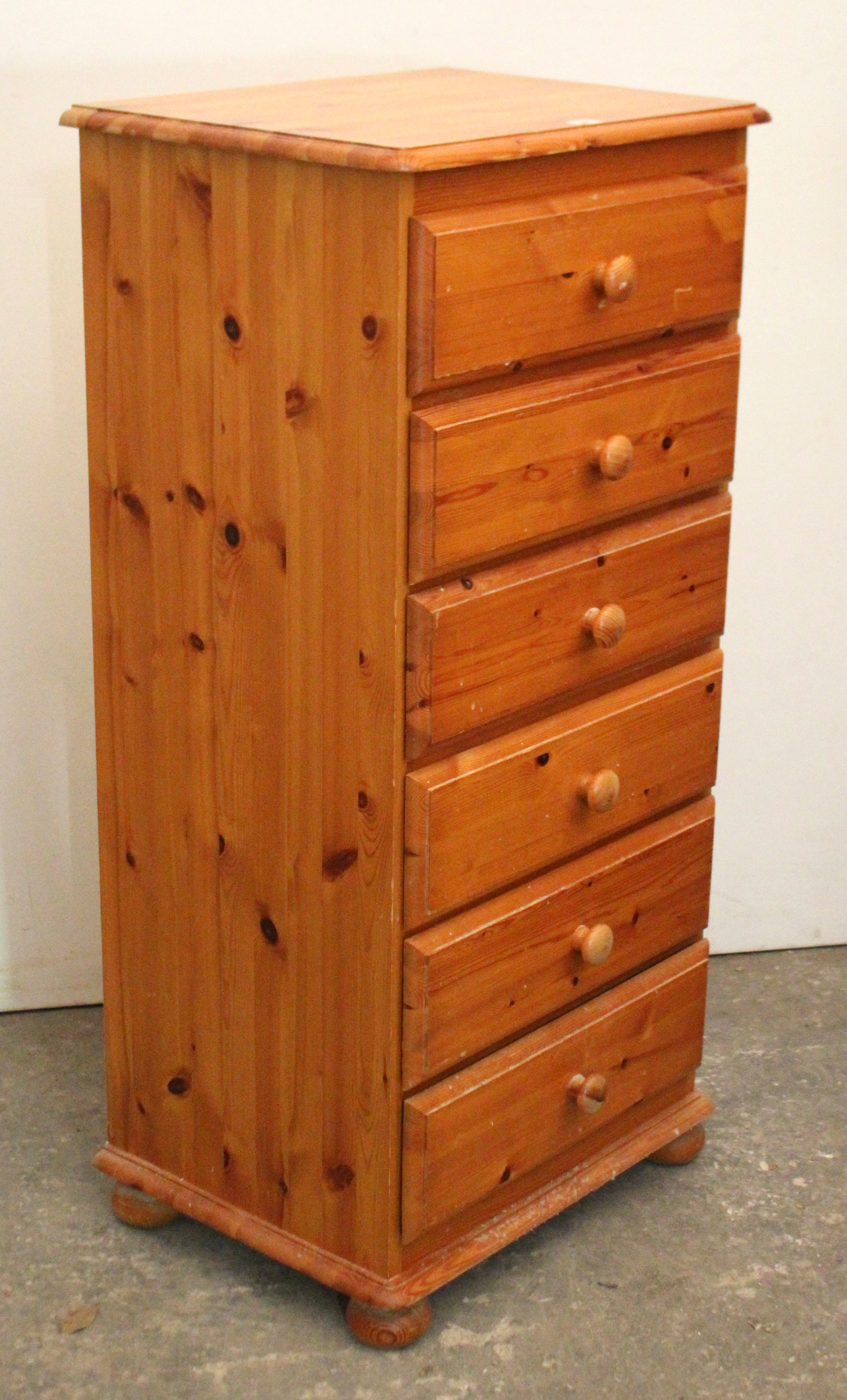 """Lot 34 - A pine upright chest fitted six long drawers with turned knob handles & on bun feet, 22½"""" wide x 47"""""""