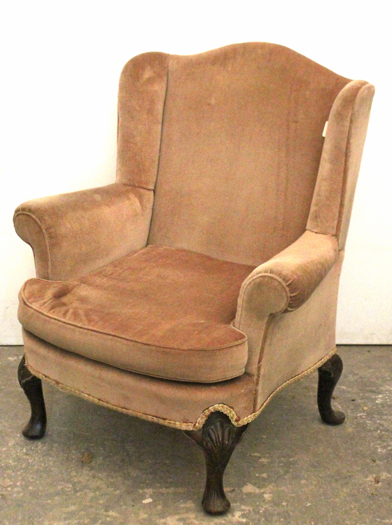 Lot 42 - A Georgian-style wing-back armchair upholstered fawn velour, & on short carved cabriole legs & pad