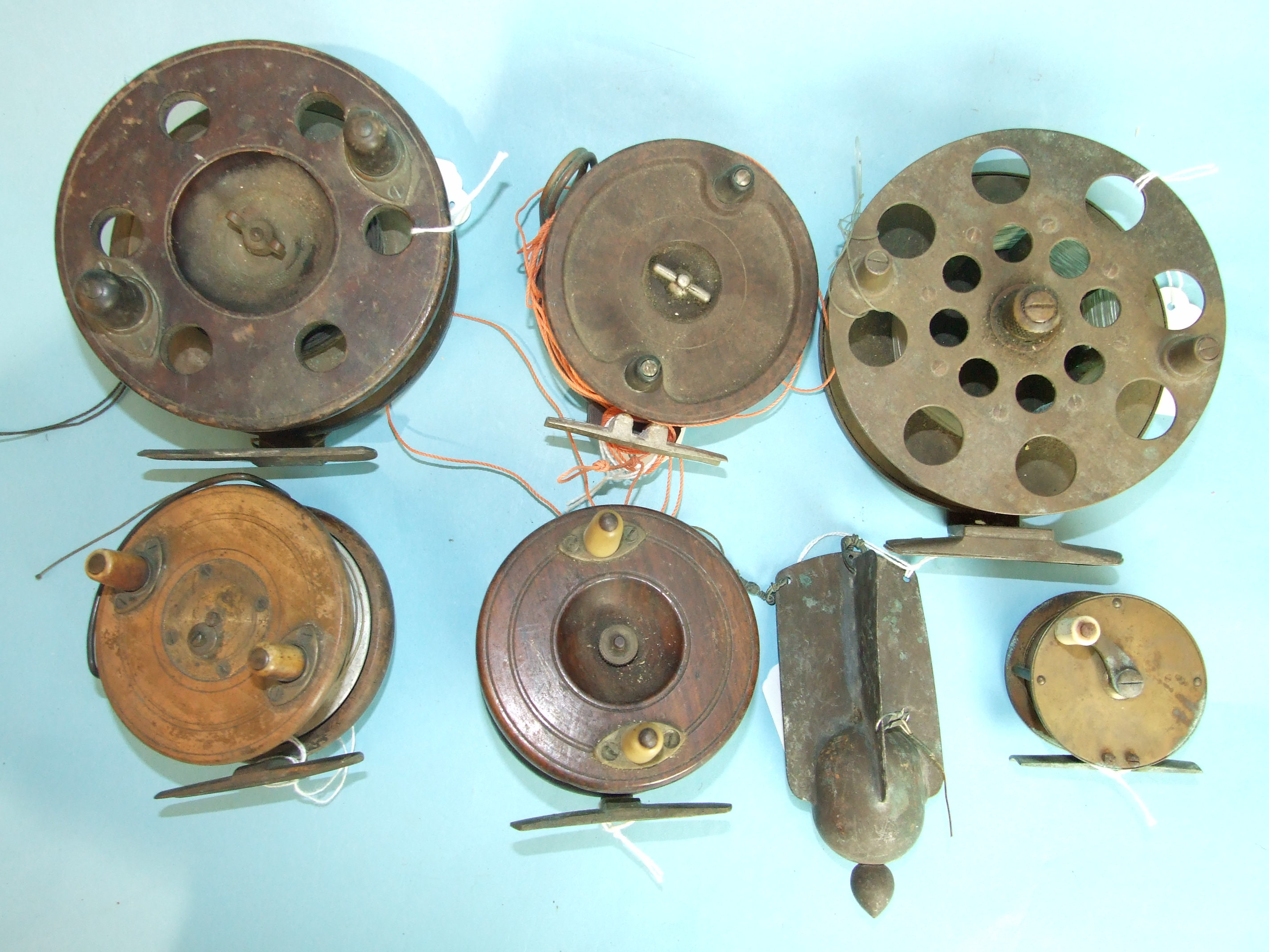 Lot 428 - Three 19th century wooden trolling reels, an Alcocks Bakelite reel, a 19th century brass winch and