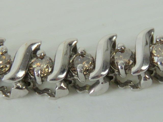 Lot 117 - A 10ct white gold and diamond tennis bracelet, forty-nine round cut diamonds,