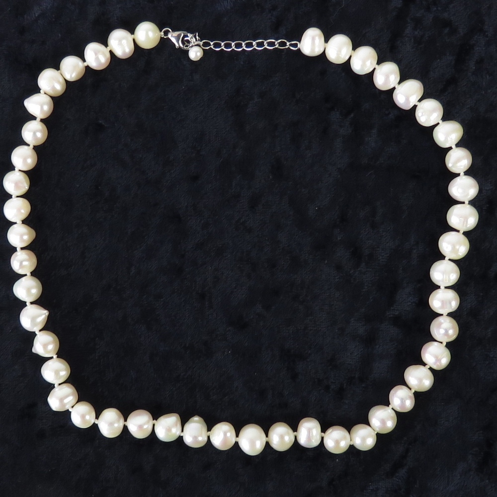 Lot 104 - A string of large white/pink baroque pearls,