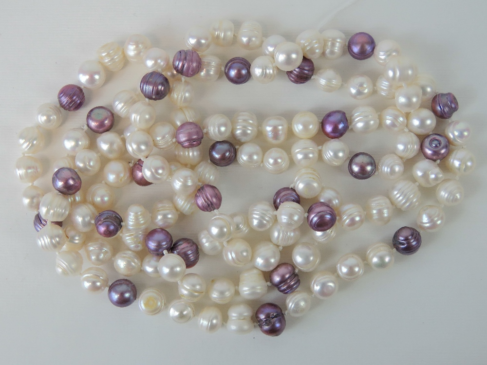 Lot 121 - A long strand of baroque pearls, lilac and white hues,