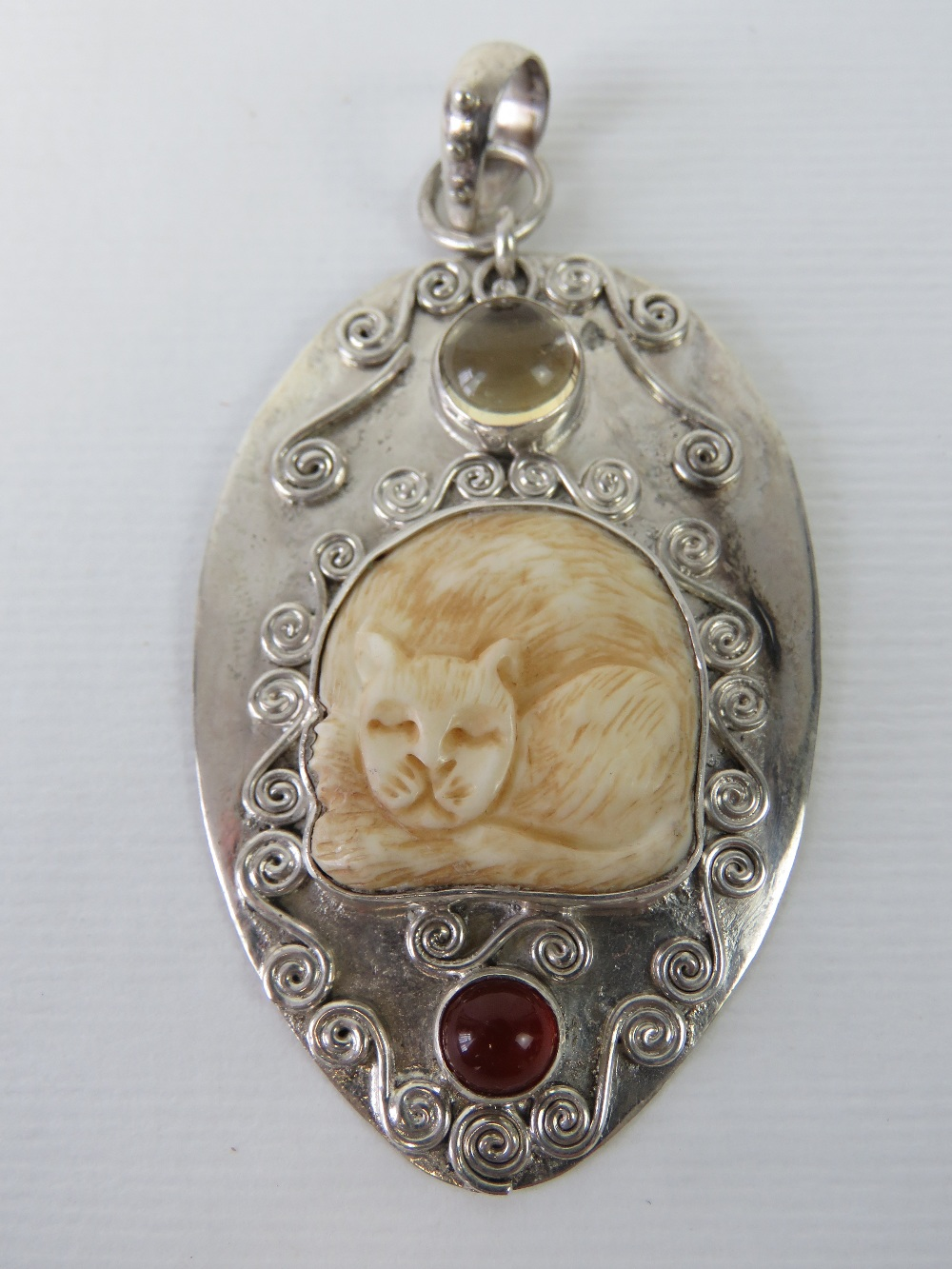 Lot 108 - An unusual silver pendant having carved bone cat and two cabachon stones upon,