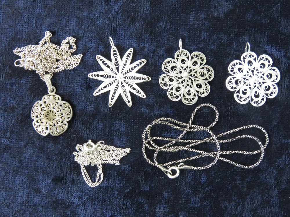 Lot 127 - Four floral filigree pendants one marked Sterling, with three silver chains.