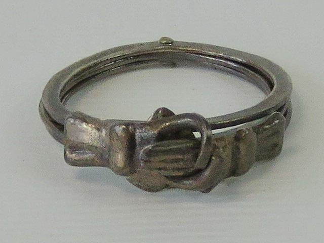 Lot 106 - An unusual ring comprising three hinged bands when closed forming two clasped hands and when open