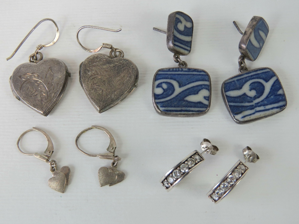 Lot 125 - Four pairs of silver earrings including; heart shaped lockets with engraved floral pattern,