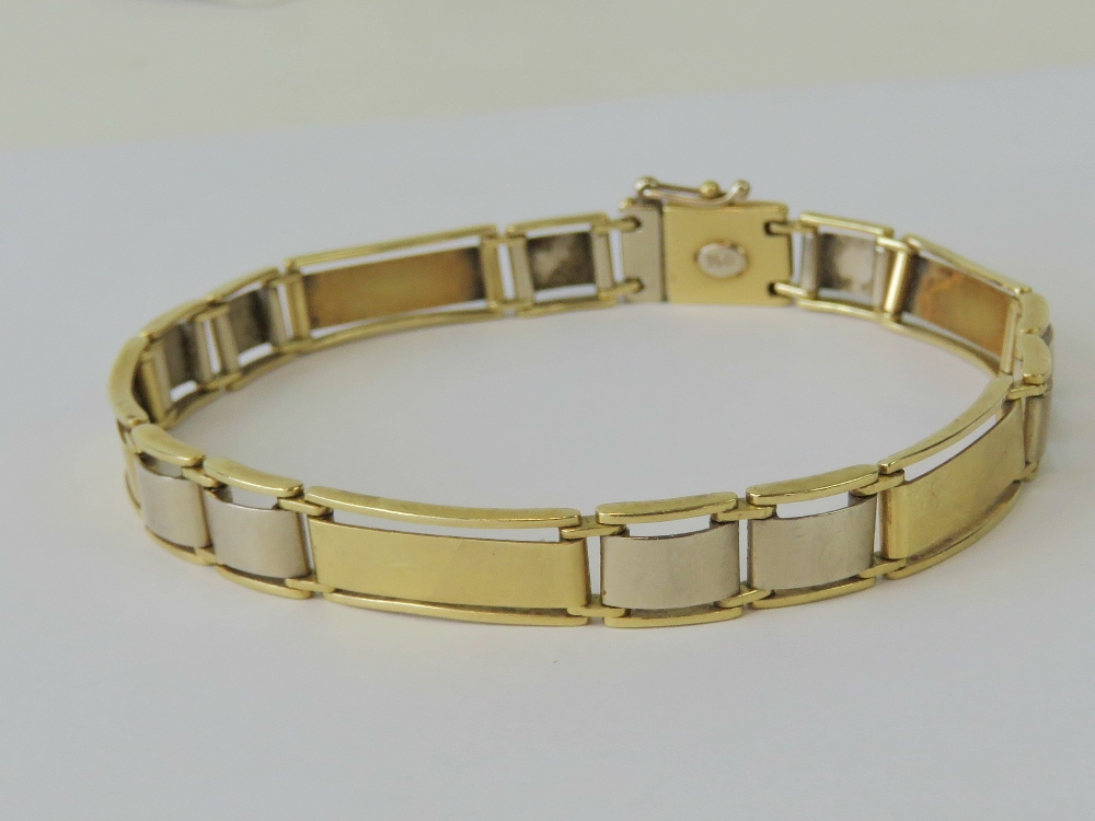 Lot 137 - An 18ct white and yellow gold alternating panel bracelet, stamped 750 with single Arabic hallmark,