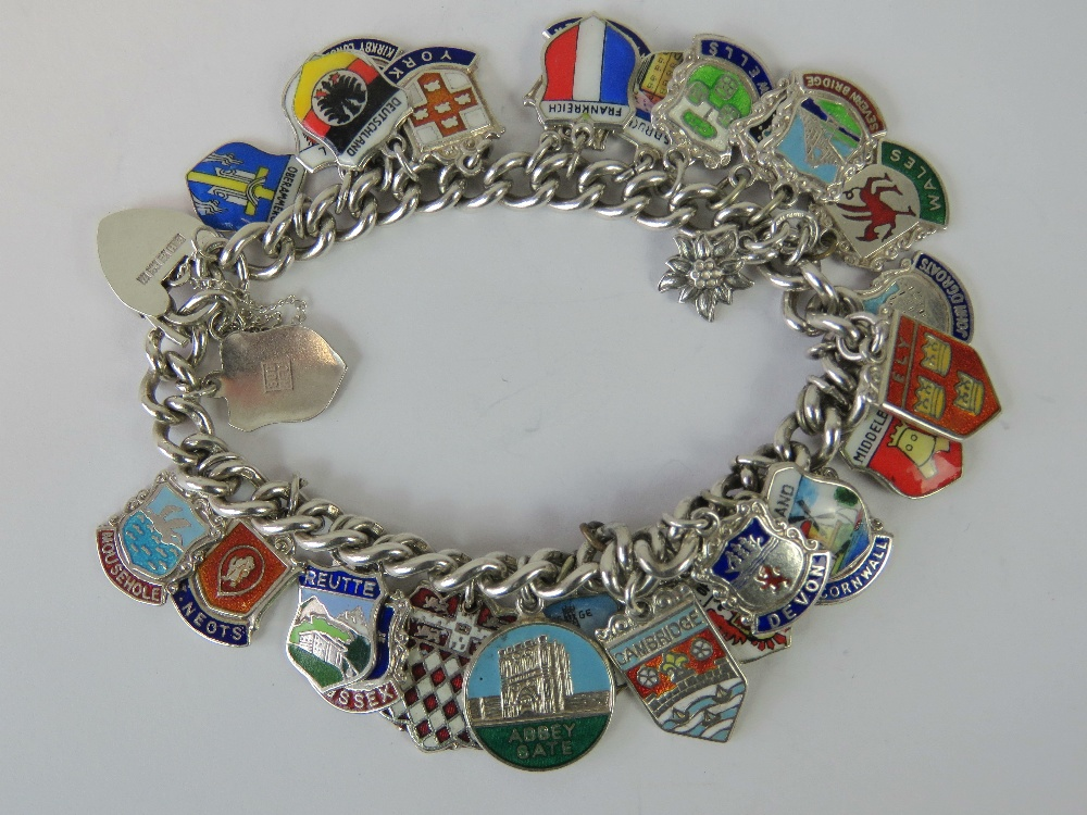 Lot 111 - A silver charm bracelet with hallmarked heart padlock clasp and a large quantity of enamelled town