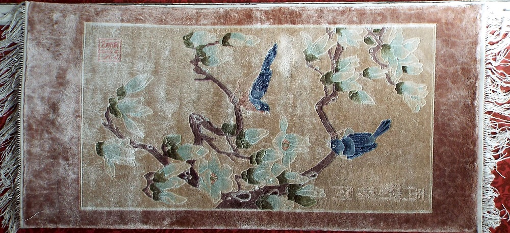 A Chinese wool prayer mat size rug decorated with birds on branches upon an ivory ground, 130 x 60