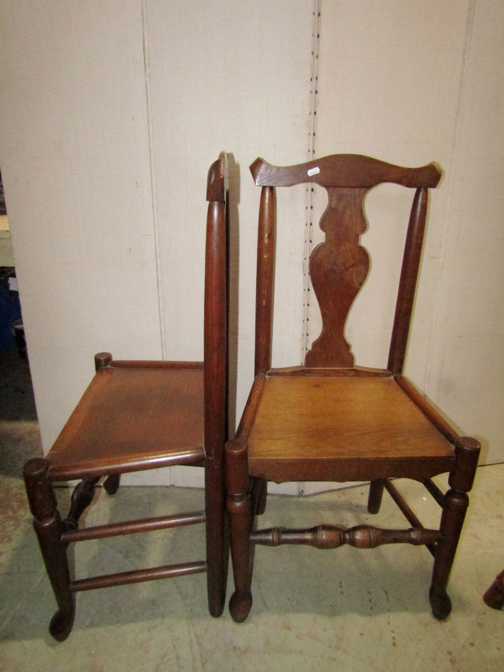 Lot 1385 - A pair of Georgian oak dining chairs with yoke shaped rails, vase shaped splats, solid seats