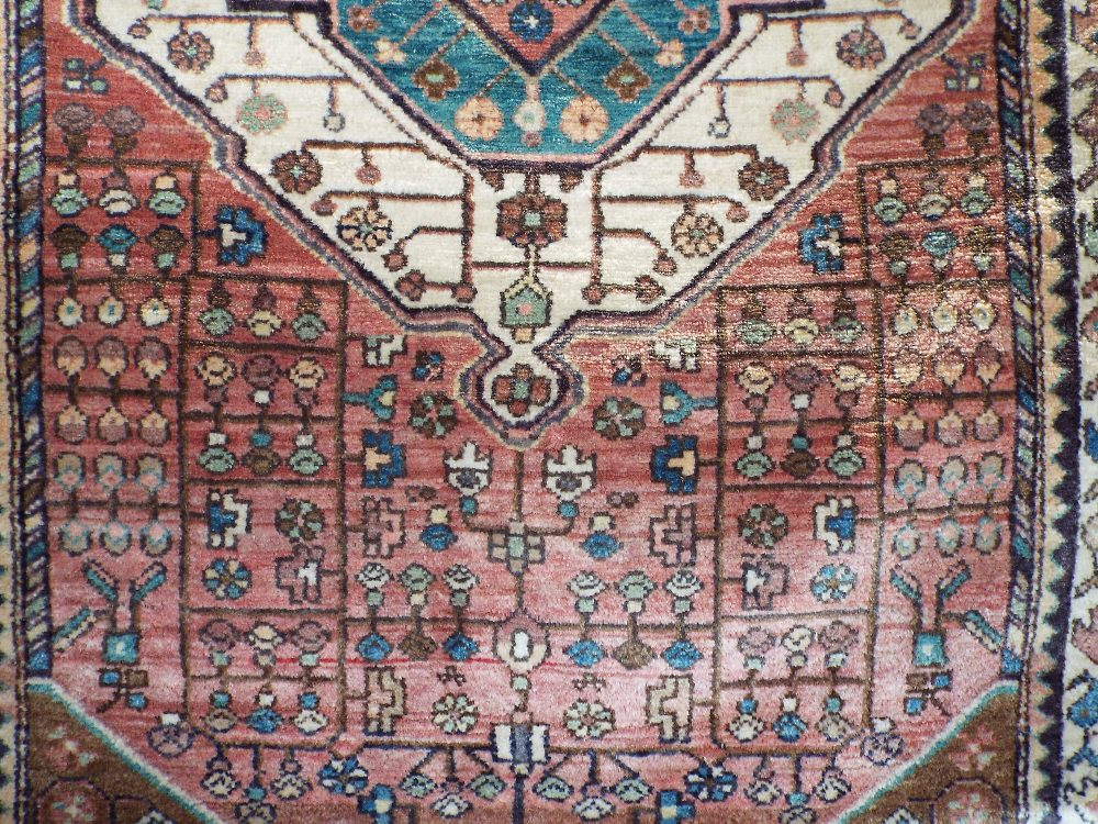 Lot 636 - Full pile Persian rug with central teal medallion upon a washed red ground, 180 x 120 cm