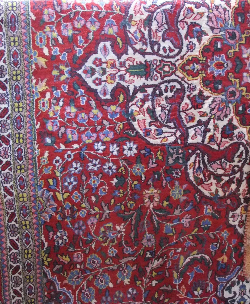 Lot 616 - Good quality Persian carpet with intricate scrolled floral decoration upon a rich red ground, 330