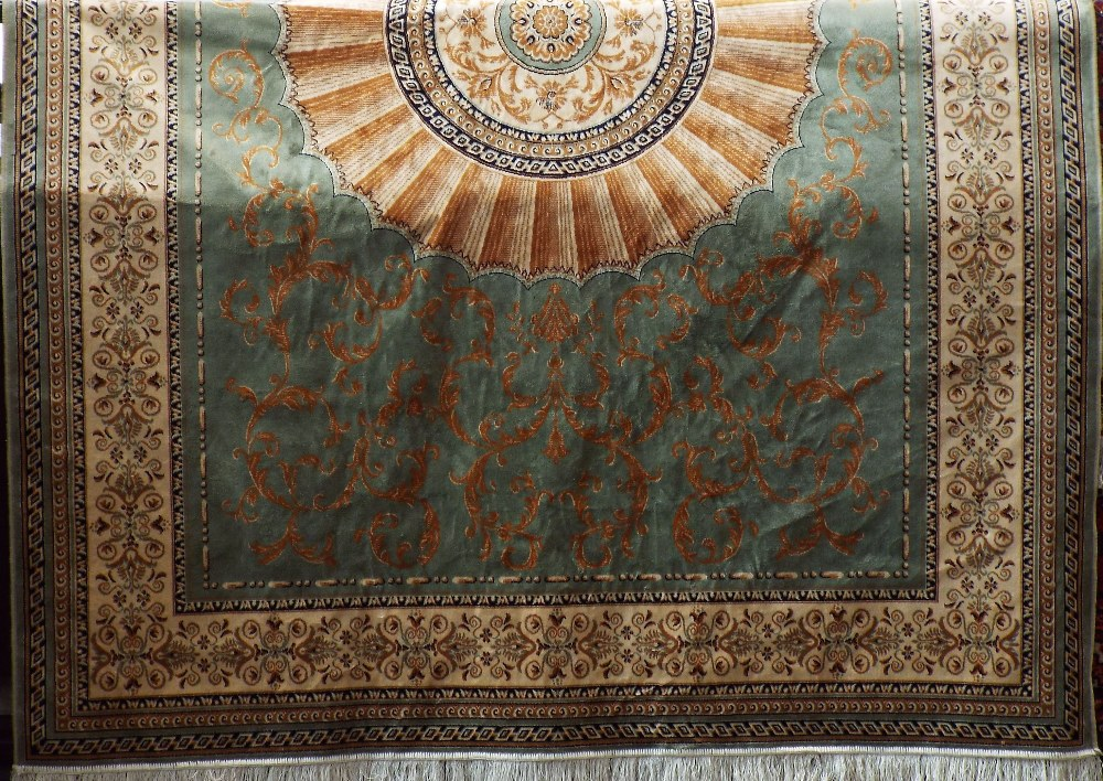 Lot 621 - Keshan style carpet with gilt sunburst medallion upon a pale green ground, 260 x 200 cm