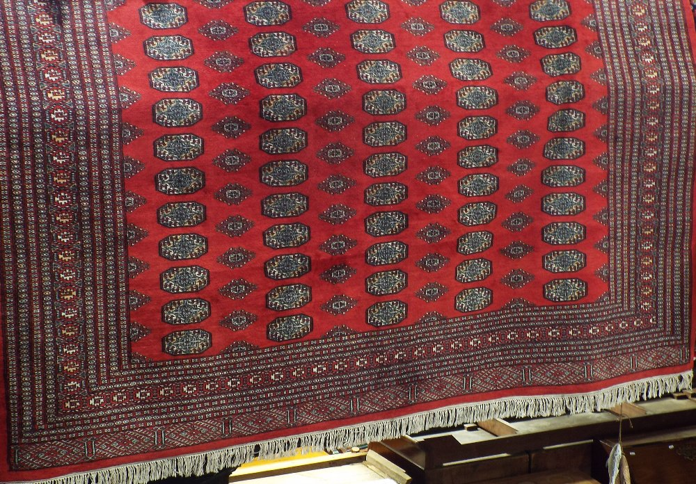 Lot 629 - Good quality Bokhara carpet with typical geometric medallion decoration upon a red ground, 300 x 260