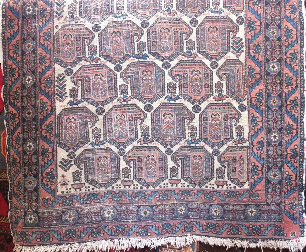 Lot 642 - Antique Persian rug decorated with multi coloured paisley type geometric motifs upon a cream ground,