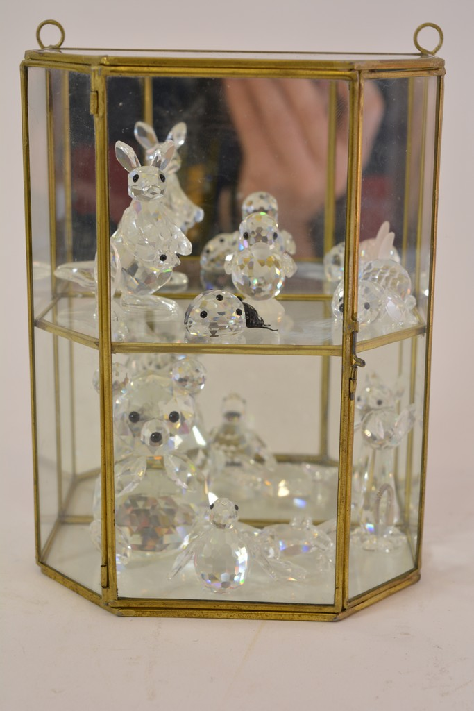 A Small Display Cabinet Containing Eight Swarovski Figures