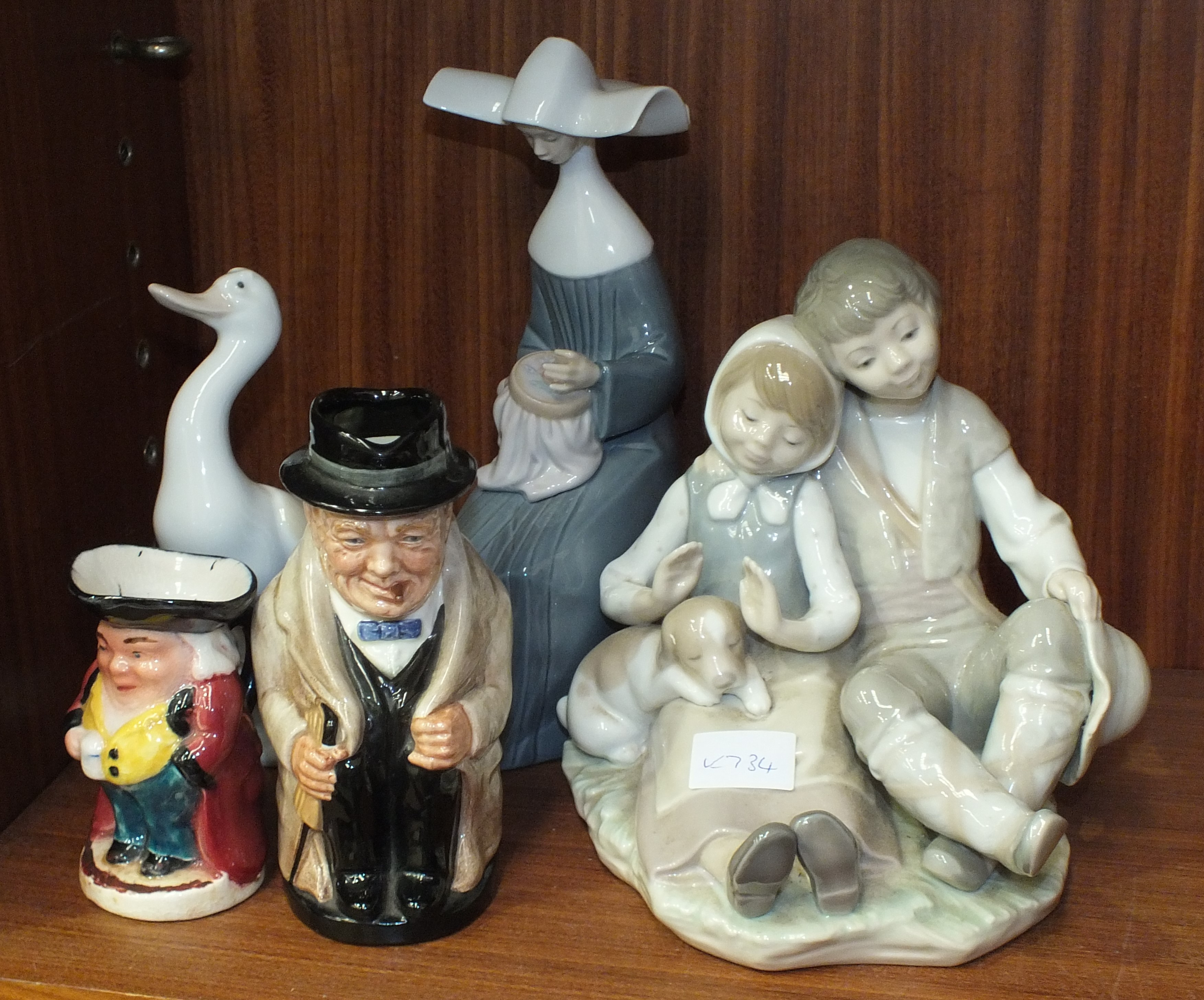 Lot 135 - A Lladro figure group of two children and a puppy, 18cm high, a Lladro figure of a seated nun,