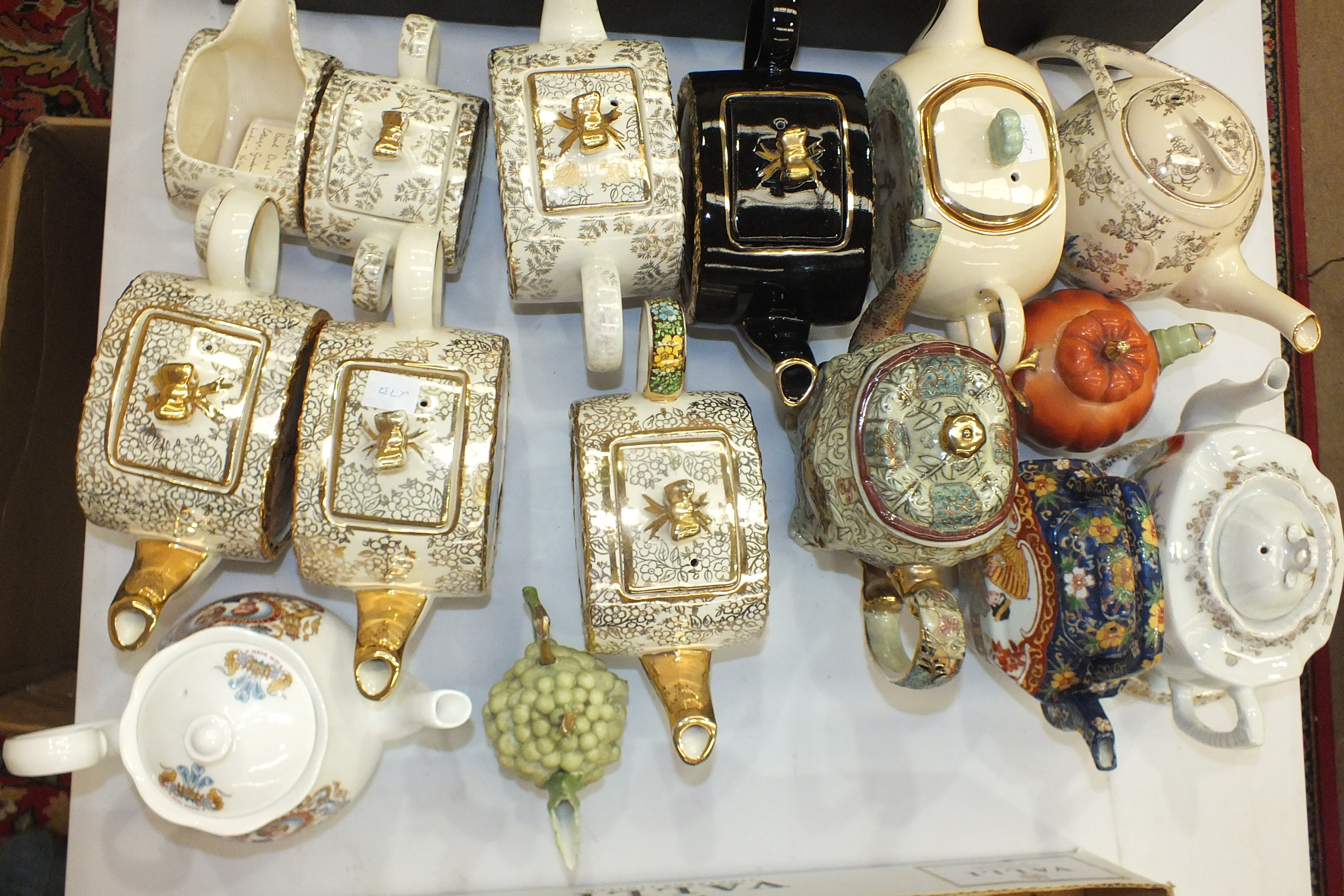 Lot 109 - A Sadlers Cottage Garden teapot, sugar basin and jug of oval form, three similar teapots and