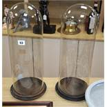 A pair of glass domes on wood stands height 48cm