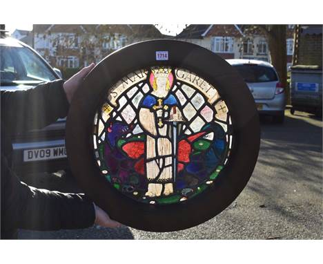 An antique stained and leaded glass roundel of St Margaret,possibly medieval, 39cm diameter, in stained pine frame.&nbs