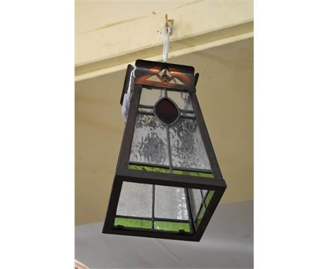 A patinated metal, stained and leaded glass lantern,25cm high.