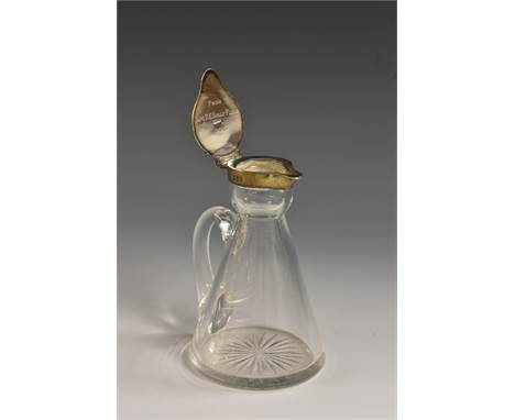 An Edwardian silver mounted clear glass whisky noggin, hinged cover, scroll handle, star-cut base, 11.5cm high, Goldsmiths &a