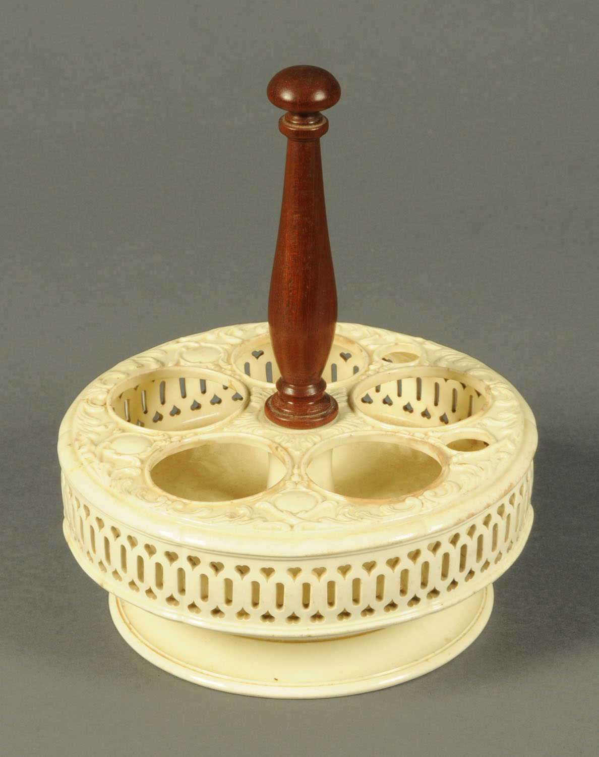 Lot 15 - An English creamware cruet stand, moulded and pierced circular form, with replacement wooden handle.