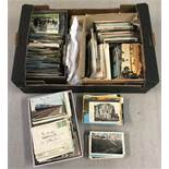 A large box of assorted vintage and modern postcards.