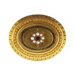 An antique Victorian ruby and pearl mourning brooch in high carat yellow gold set with an oval cut