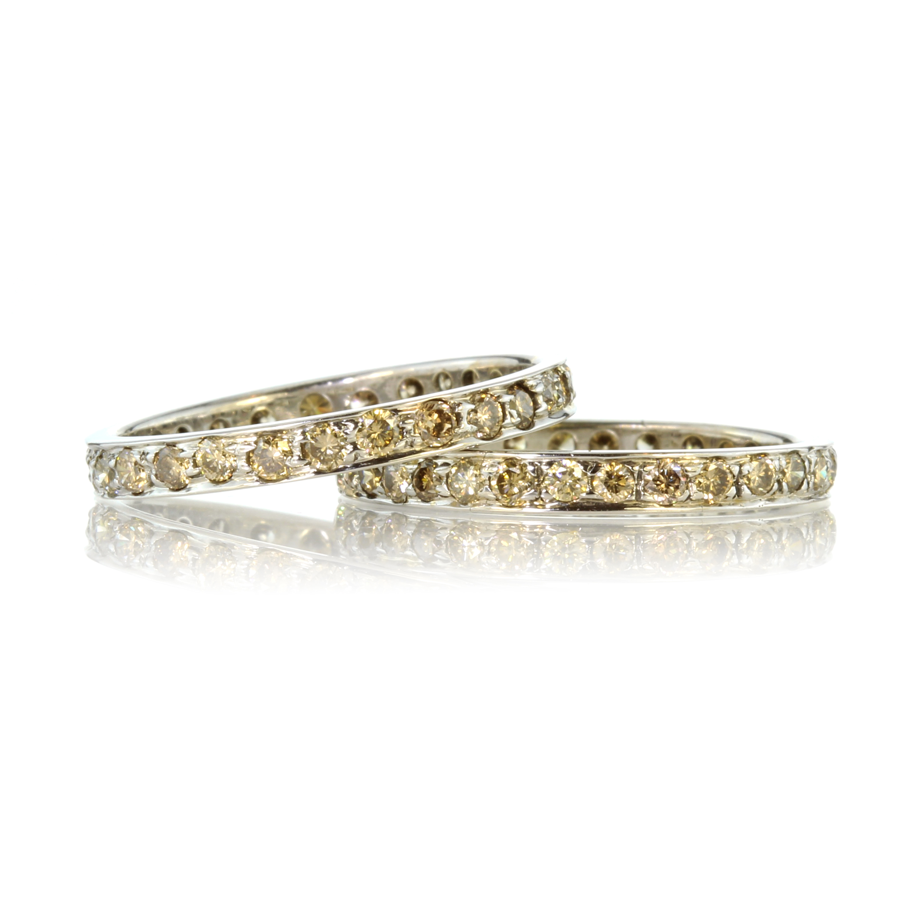 Los 48 - A pair of yellow diamond eternity rings in white gold each set with round cut yellow diamonds.