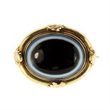 An antique Victorian banded agate mourning brooch the large cabochon measuring 25x19mm, surrounded