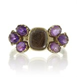 An antique Georgian hairwork and amethyst mourning ring in high carat yellow gold designed as a