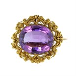 An antique 19th Century amethyst brooch in yellow gold set with a large oval cut amethyst weighing