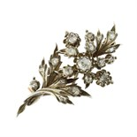 An antique jewelled diamond floral spray brooch in gold and silver designed as a spray of flowers