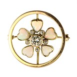 An opal and diamond flower brooch in high carat yellow gold set with a central round cut diamond