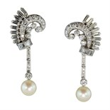 A pair of French diamond and pearl cocktail earrings in platinum each designed as a scrolling