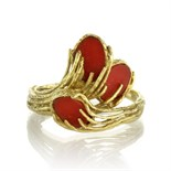 A vintage coral dress ring in 18ct yellow gold set with three oval panels of coral within a textured