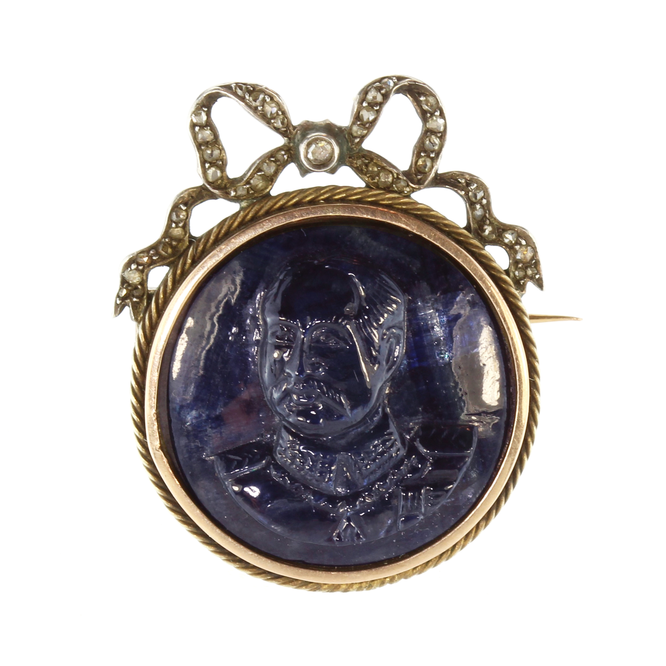 Los 40 - A French sapphire cameo and diamond brooch in gold and silver set with a large, circular carved blue