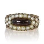 An antique Georgian garnet and seed pearl ring in high carat yellow gold set with an elongated