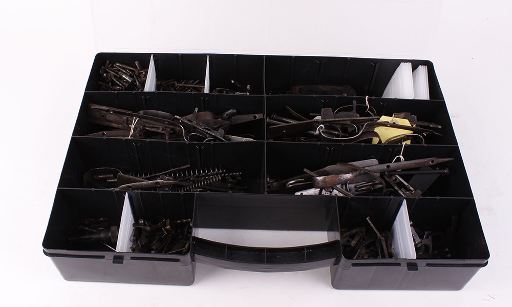 Lot 36 - Large compartment box of various shotgun parts and components: Triggers, trigger guards, screws,