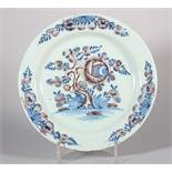 "An 18th century English delft plate with peony decoration in manganese and blue, 8 7/8"" dia (hair"