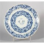 An early 18th century Bristol delft plate with swag and scroll decoration, inscribed monogram ""