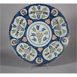 An 18th century Bristol delft charger with central floral panel and reserved panels of flowers on