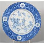 An 18th century London delft plate with scratched and reserved flower decoration, Oriental figure in