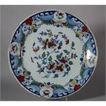 "An 18th century Bristol delft charger with spray of flowers and insect decoration, monogram ""WP"" for"